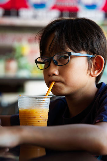 Portrait of boy drinking juice on table in cafe