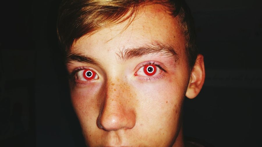 Portrait Of Boy With Red Eyes Against Black Background