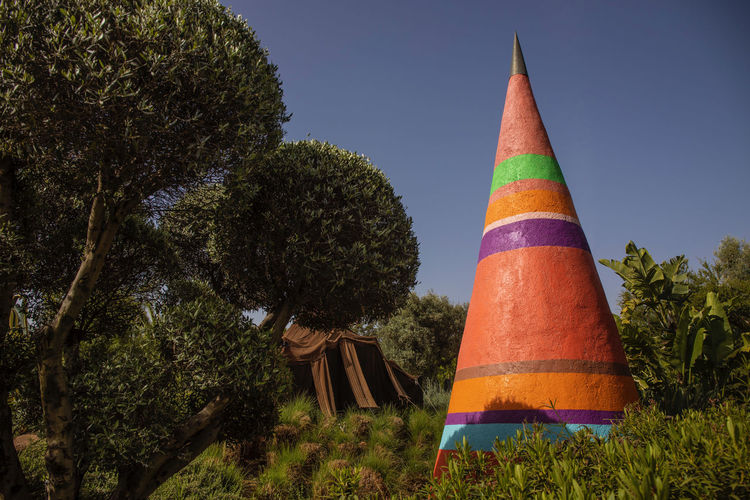 a very imaginative garden space outside of Marrakech, Morocco with beautiful and colourful objects blending with the garden Garden Park Colorful ArtWork Trees Path Imaginative Marrakech Morocco Anima Garden Textured  Tree Plant No People Cone Nature Multi Colored Art And Craft Outdoors Sky Growth Day Green Color Striped Architecture Grass Creativity Land Beauty In Nature Flag Traffic Cone