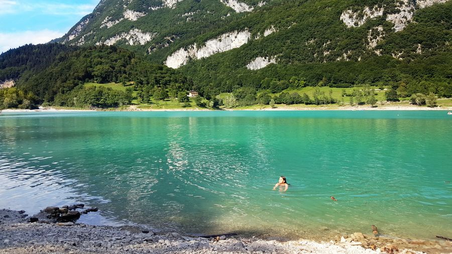 Woman swimming in lake against mountain