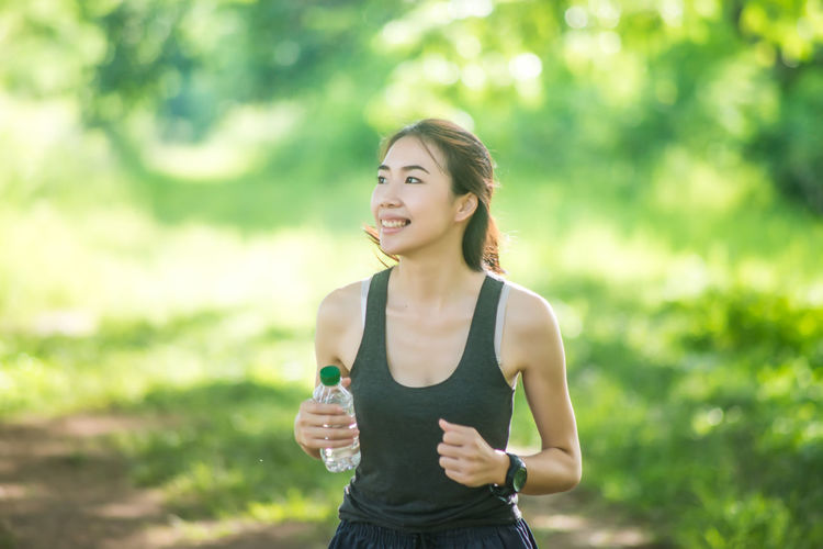 Adult Beautiful Woman Clothing Day Emotion Focus On Foreground Front View Green Color Hairstyle Happiness Healthy Lifestyle Lifestyles One Person Outdoors Real People Smiling Standing Tank Top Waist Up Women Young Adult Young Women