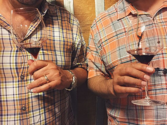Midsection Of Friends Holding Wineglasses