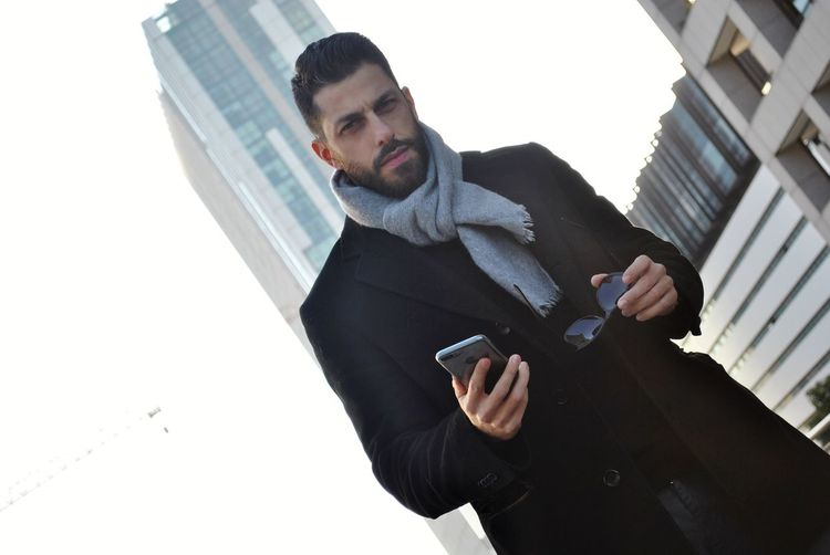 Portrait of man with mobile phone in city