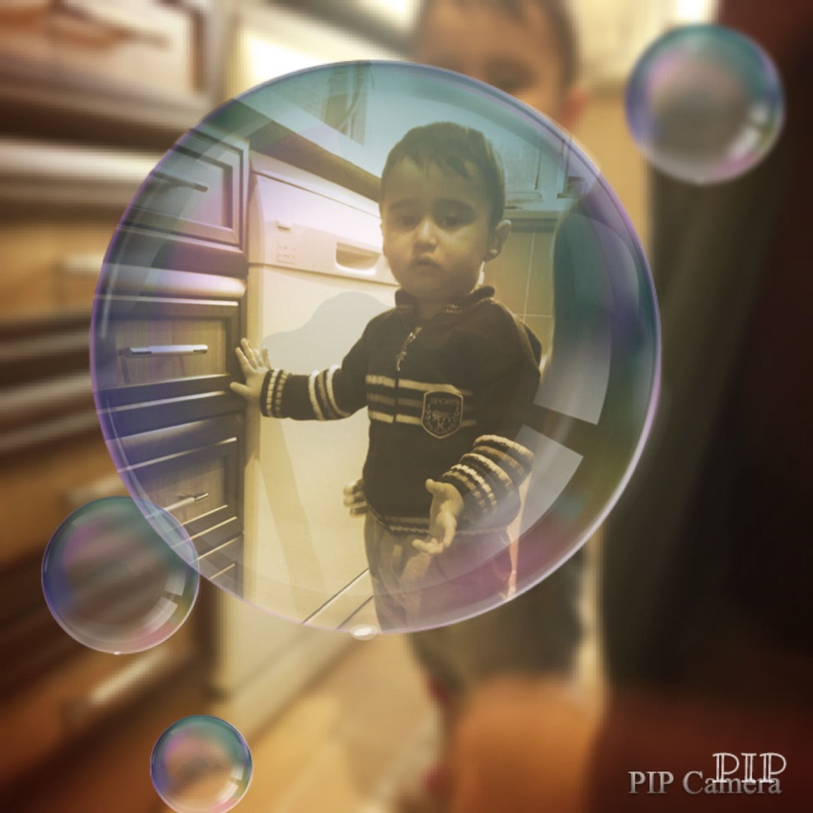 leisure activity, indoors, lifestyles, arts culture and entertainment, playing, focus on foreground, childhood, holding, fun, boys, enjoyment, reflection, men, circle, technology, close-up, transparent, glass - material