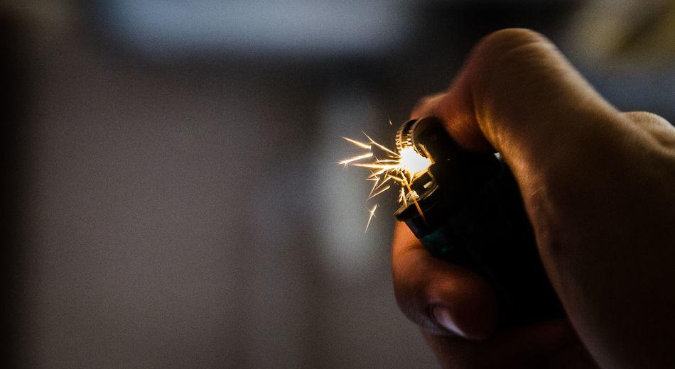 Cropped hand igniting cigarette lighter in darkroom