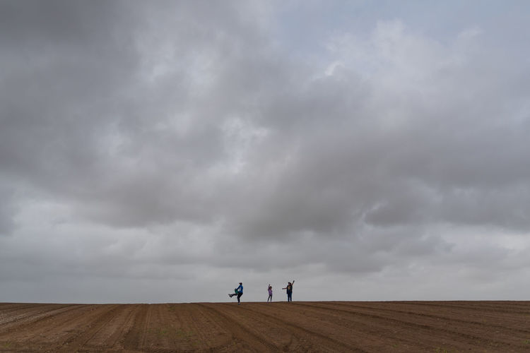 People standing on land against cloudy sky