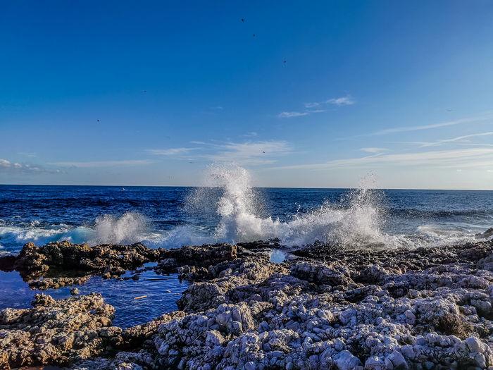Waves splashing on rocks at shore against sky