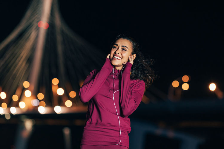 Portrait of smiling woman standing against illuminated city at night