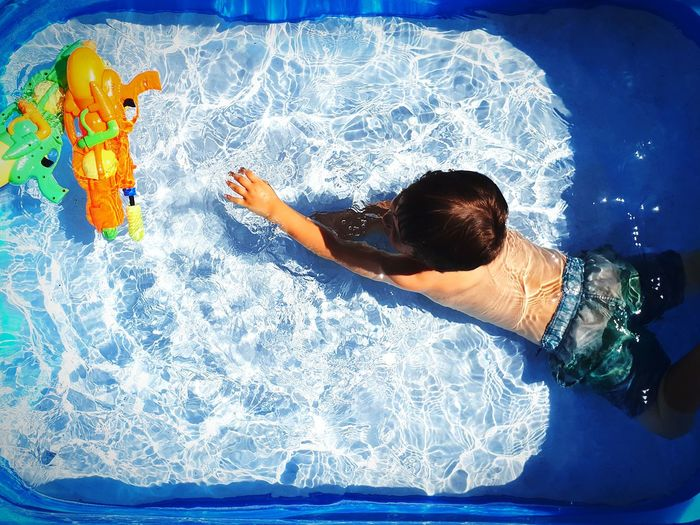 High Angle View Of Boy With Toys Swimming In Wading Pool
