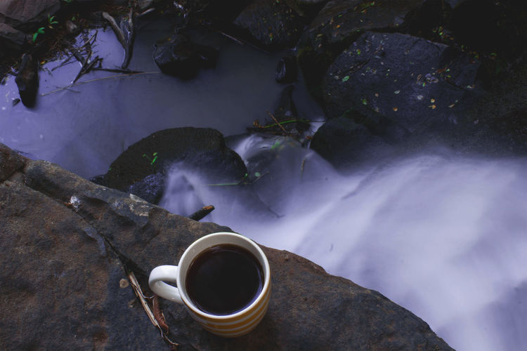 High Angle View Of Black Coffee On Rock By Waterfall