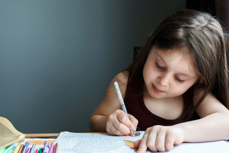 Close-up of cute girl drawing on book at home