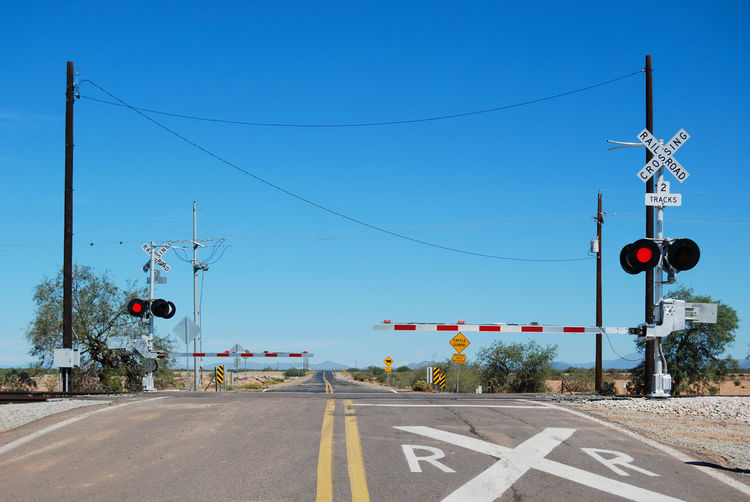 Railroad crossing in Arizona with the gates down before train passes by Asphalt Blue Country Road Day Diminishing Perspective Double Yellow Line Empty Empty Road FlashingLights Gates Guidance Information Information Sign No People Outdoors Pole Red Road Road Marking Road Sign RR Crossing Sky The Way Forward Tracks Vanishing Point