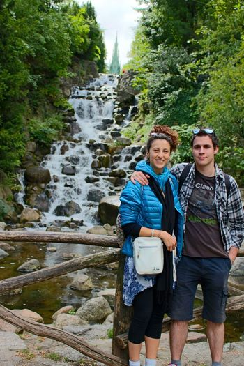 Portrait of happy friends standing against waterfall at viktoriapark