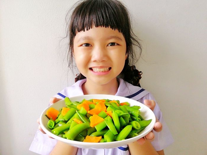Portrait of a smiling girl holding food