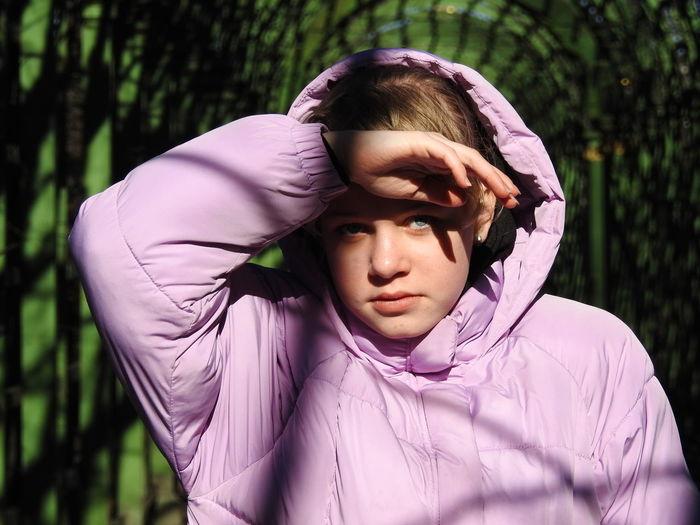 Portrait of girl hood against plants
