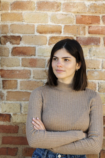 Portrait of a woman against brick wall