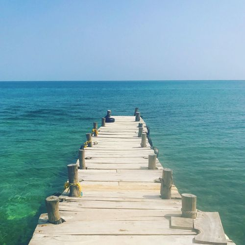 EyeEmNewHere Beauty In Nature Blue Clear Sky Day Fishing Pole Horizon Over Water Jetty Nature Outdoors Real People Scenics Sea Sky The Way Forward Tranquil Scene Tranquility Water Wood Paneling Lost In The Landscape