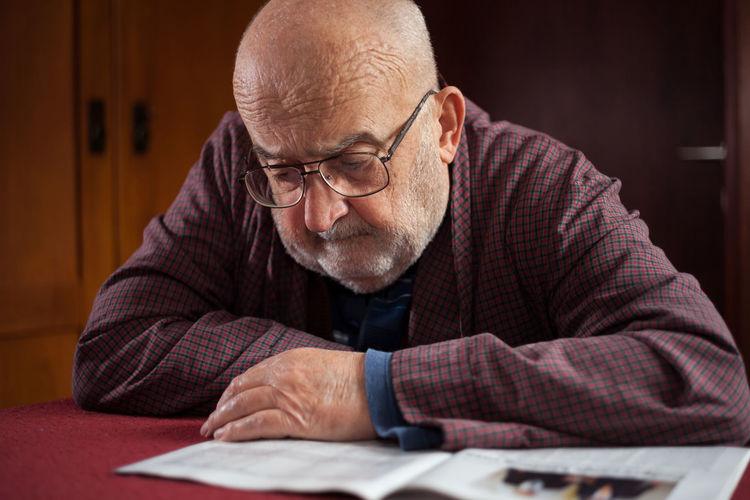 pensioner reading newspaper Beard Close-up Comfort Elderly Eyeglasses  Gentleman  Home Interior Indoors  Information Journal Leisure Activity Lifestyles Magazine News Newspaper Pensioner People Reader Reading Retirement Seated Senior Men Serious Sitting Table