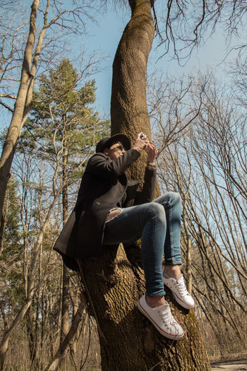 Man sitting on tree trunk against bare trees