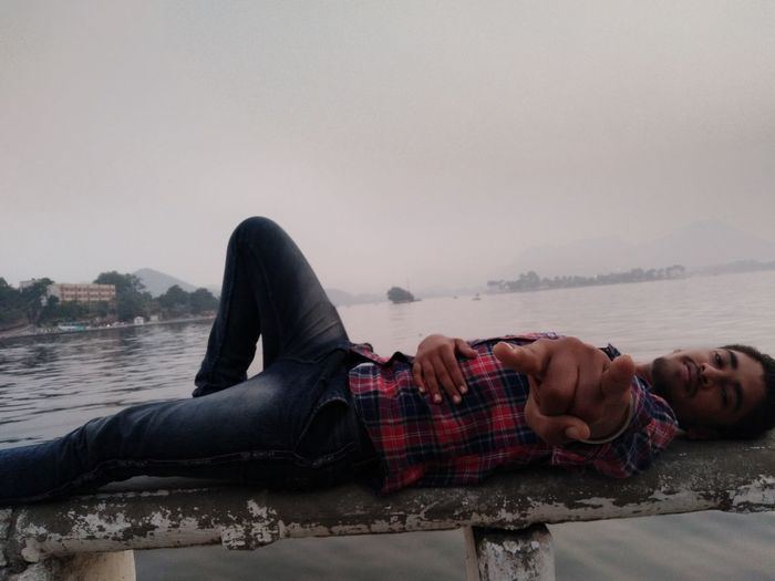 Portrait of young man lying down against sky