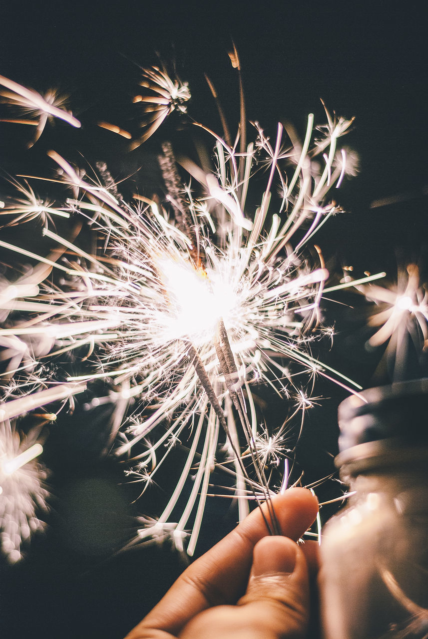 human hand, hand, holding, real people, human body part, firework, illuminated, sparkler, motion, lifestyles, celebration, burning, one person, glowing, event, finger, human finger, sparks, body part, night, firework - man made object, firework display, light