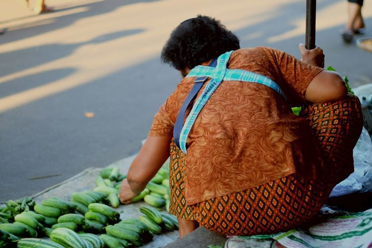 Rear view of woman selling cucumbers on street