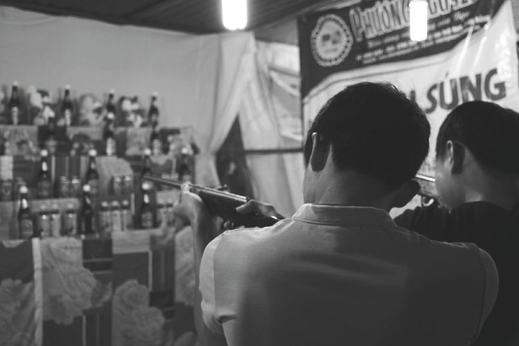 Rear view of friends aiming wine bottles with gun