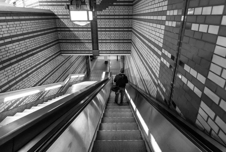 High Angle View Of Man Moving Down On Escalator At Subway Station