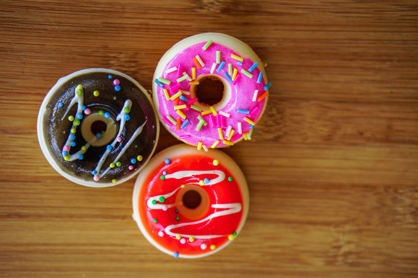 Food Sweet Food Food And Drink Multi Colored Sweet Baked Indulgence Wood - Material Table Donut No People Still Life Indoors  Directly Above Sprinkles Dessert Temptation Unhealthy Eating Close-up Cookie Icing Snack