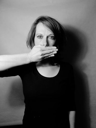 Portrait Of Woman Covering Mouth While Standing Against Wall