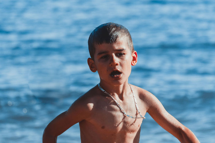 Shirtless boy walking against sea