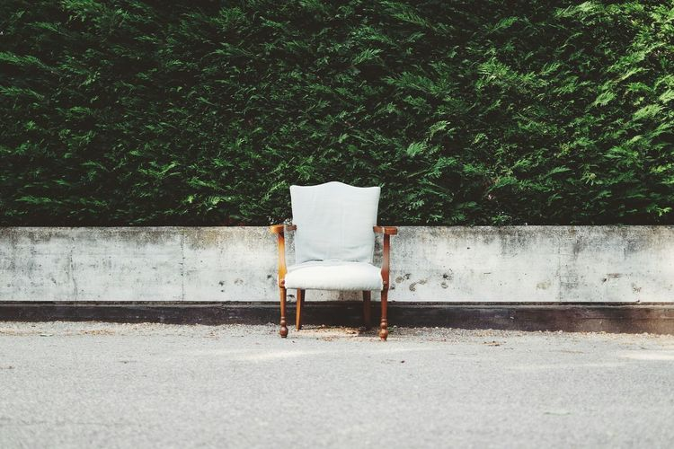 Wooden armchair on street in front of lush green leaves