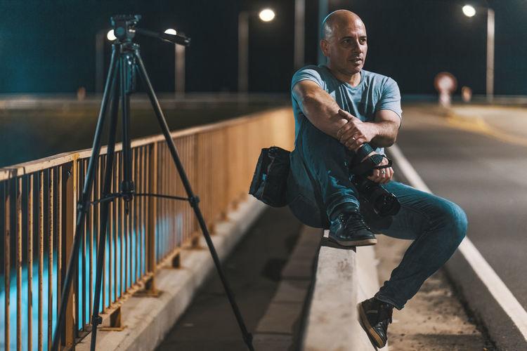Man holding camera sitting by railing at night