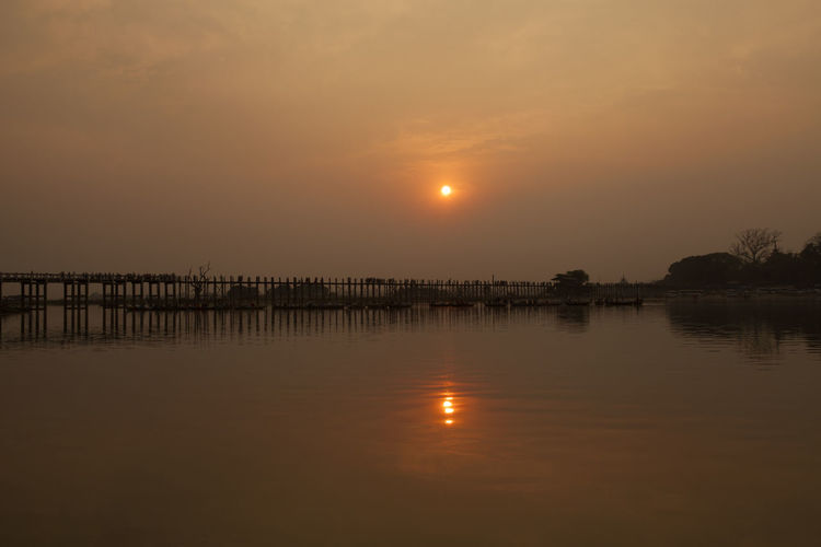 U bein bridge over taungthaman lake against sky during sunset
