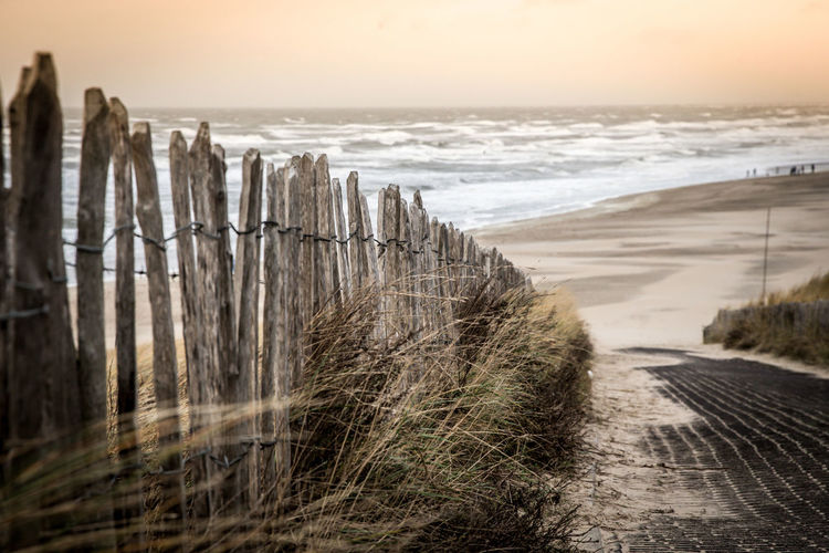 Walk to the beach Sea Water Sky Beach Land Nature Horizon Over Water Horizon Scenics - Nature Beauty In Nature Wave Motion Aquatic Sport No People Tranquility Tranquil Scene Sunset Fence Outdoors Wooden Post