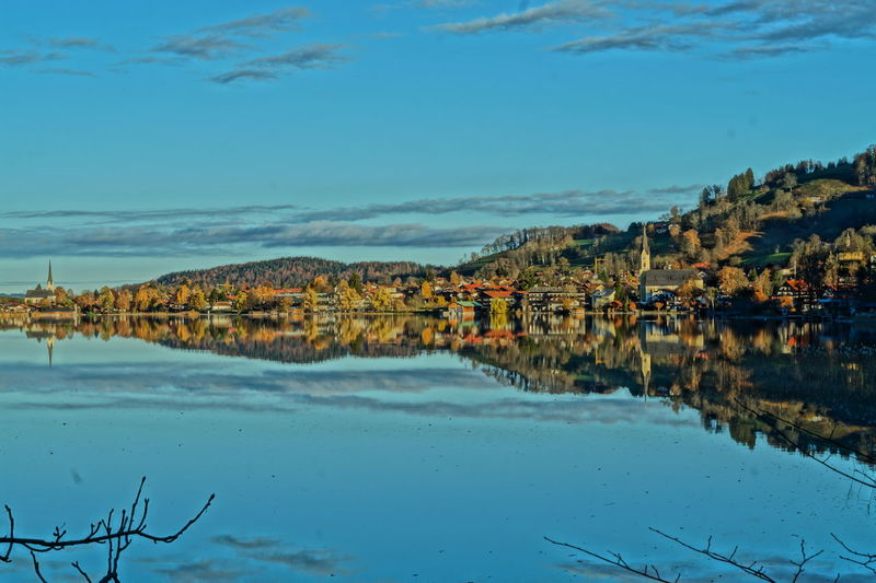 Houses and trees reflecting in lake against sky