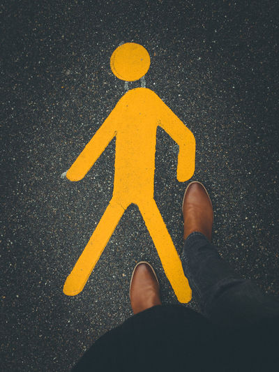 pedestrian sign on pavement with brown leather boot Sign Road Guidance Human Body Part Symbol Yellow Body Part Transportation City One Person Low Section Communication High Angle View Shoe Road Sign Standing Arrow Symbol Direction Street Road Marking Human Limb Human Foot Pedestrian Pedestrian Walkway Pedestrian Crossing Sign