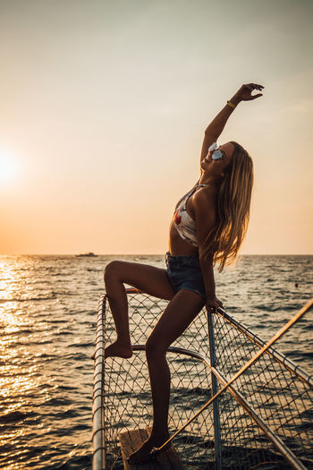 Water Sky Sunset Sea Real People Lifestyles One Person Leisure Activity Horizon Over Water Beauty In Nature Nature Scenics - Nature Horizon Young Adult Full Length Women Young Women Transportation Arms Raised Sun Human Arm Outdoors Hairstyle