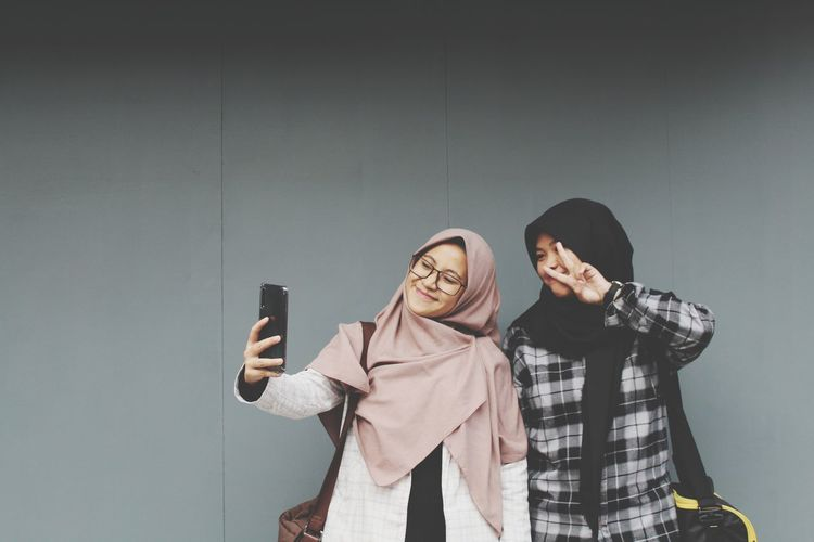 View of young women taking selfie by wall outdoors