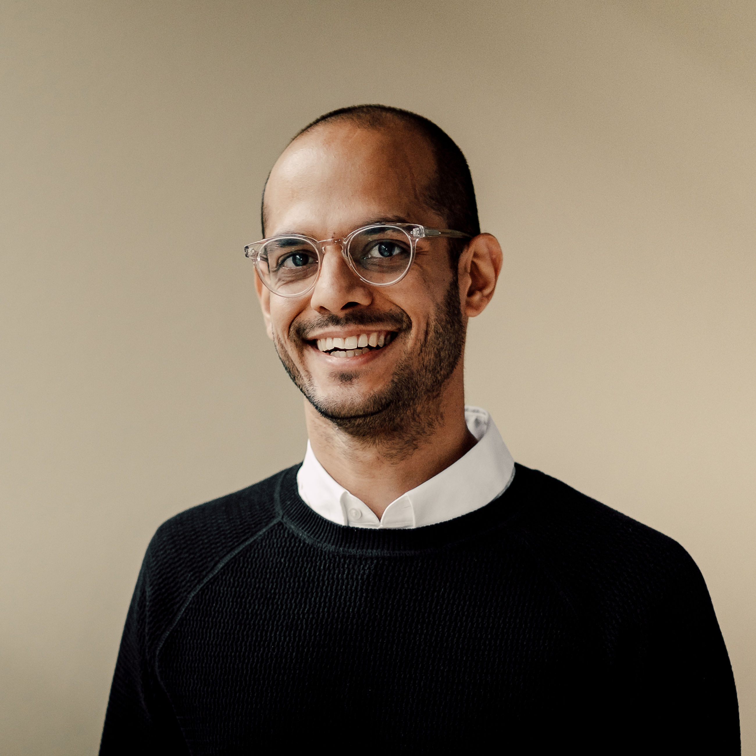 portrait, looking at camera, only men, one man only, one young man only, studio shot, young adult, one person, individuality, adults only, eyeglasses, real people, shaved head, confidence, adult, people, close-up, smiling, day