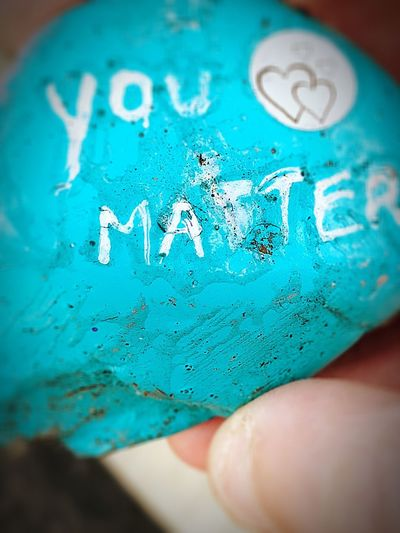 """""""You Matter"""" 💜 I found this inspiring message painted on a rock outside the bank. I needed to hear that at that particular moment. 🙏 Serendipity Handheld Message Symbol Sign Value Heart Inspirational Macro Kindness Love Positive Vibes Art And Craft Art, Drawing, Creativity Painted Inspired Words Words In The Wild Typography You Matter Turquoise Colored Stone Rock Human Hand Hand Close-up Personal Perspective Holding Western Script"""