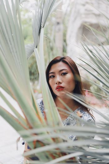 Portrait of young woman standing against plants in park