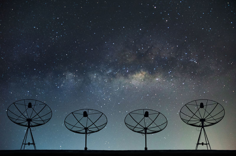 Low angle view of satellites against star field at night