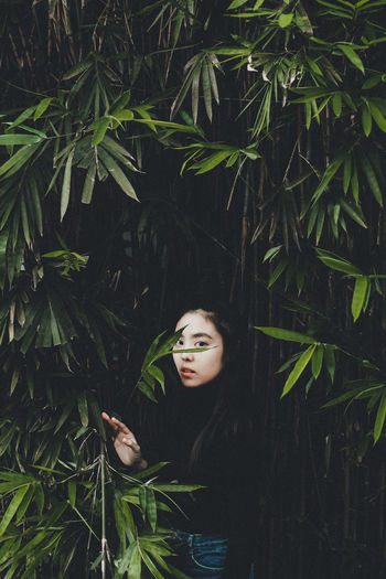 Young woman standing by plants