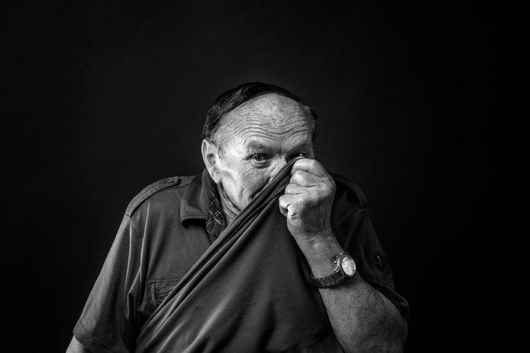Portrait of senior man hiding face while standing against black background