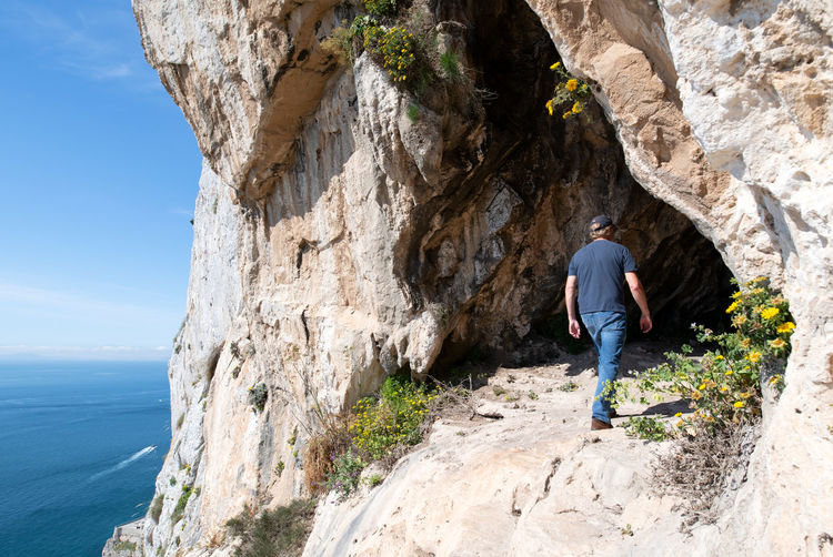 Man exploring one of the goats hair twin caves in gibraltar