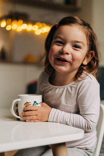 Portrait of a smiling young woman drinking coffee