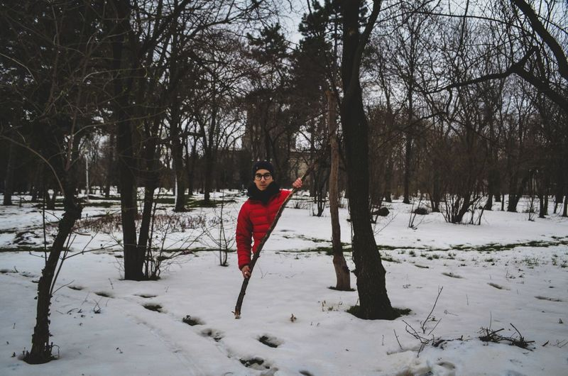 Digital composite image of man standing behind stick on snow covered field at forest