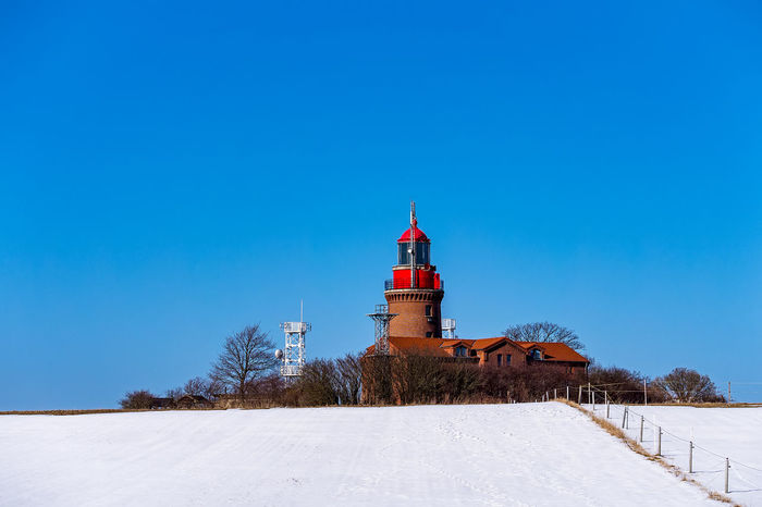 Kuehlungborn Kühlungsborn, Germany Architecture Bastorf Beauty In Nature Blue Building Exterior Built Structure Bük Clear Sky Cold Temperature Copy Space Day Guidance Landmark Lighthouse Nature No People Outdoors Sky Snow Tower Travel Destinations Tree Winter