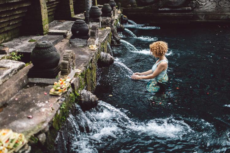 Full length of woman splashing water